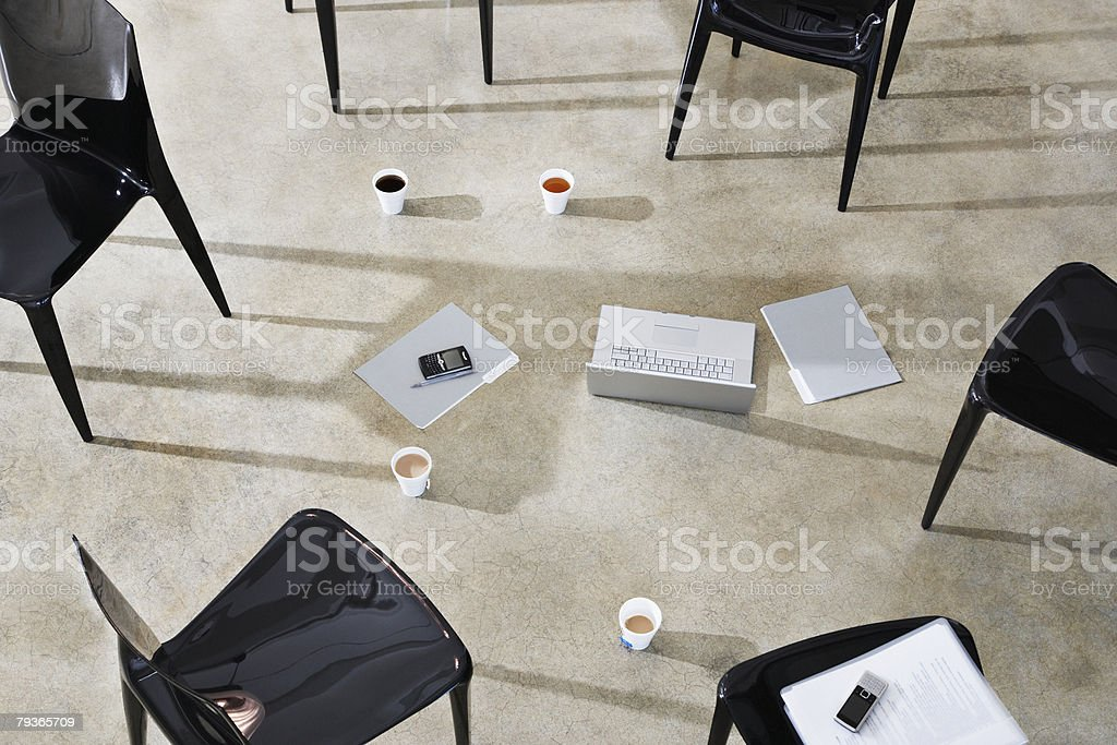 Six empty chairs indoors around a laptop and folders stock photo