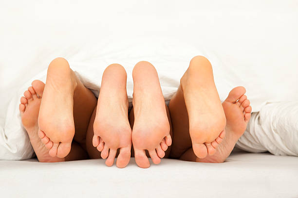 six feet while threesome in bed stock photo