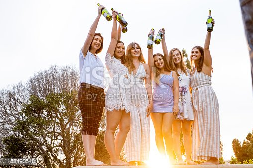Six college roommates/sorority sisters celebrate graduation by popping champagne and toasting the bottles together with arms extended above their heads. The sun shines brightly between their legs as it sets.