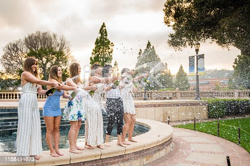 Six college roommates/sorority sisters celebrate graduation by popping champagne and spraying it everywhere while standing on the ledge next to a fountain.