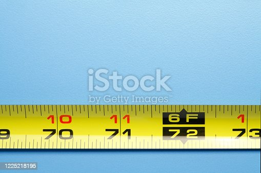 A close up of the six foot mark on a tape measure that represents the accepted distance required for social distancing on a blue background.