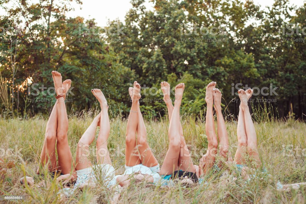 Six girls lie on the grass and raise their legs up stock photo