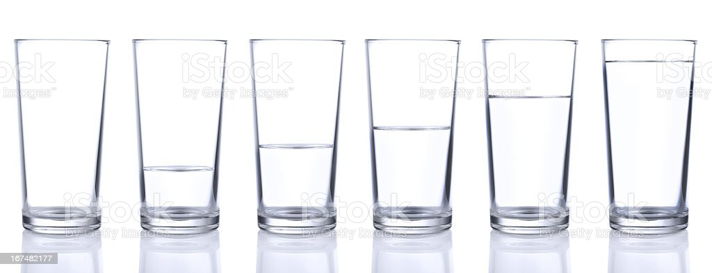 Six glasses with different levels of water stock photo