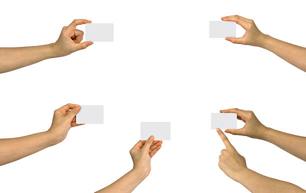 Six hands holding up five blank business cards stock photo
