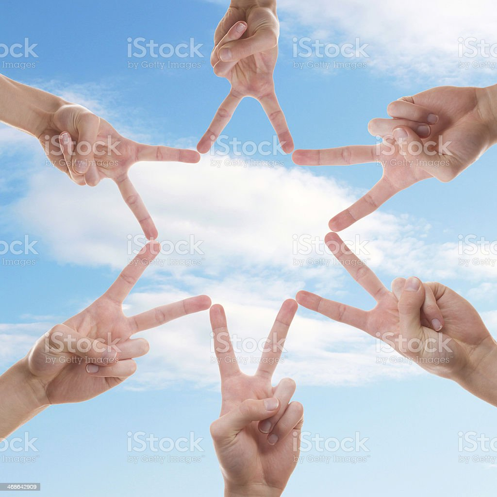 Six hands making a star in the sky with their fingers stock photo