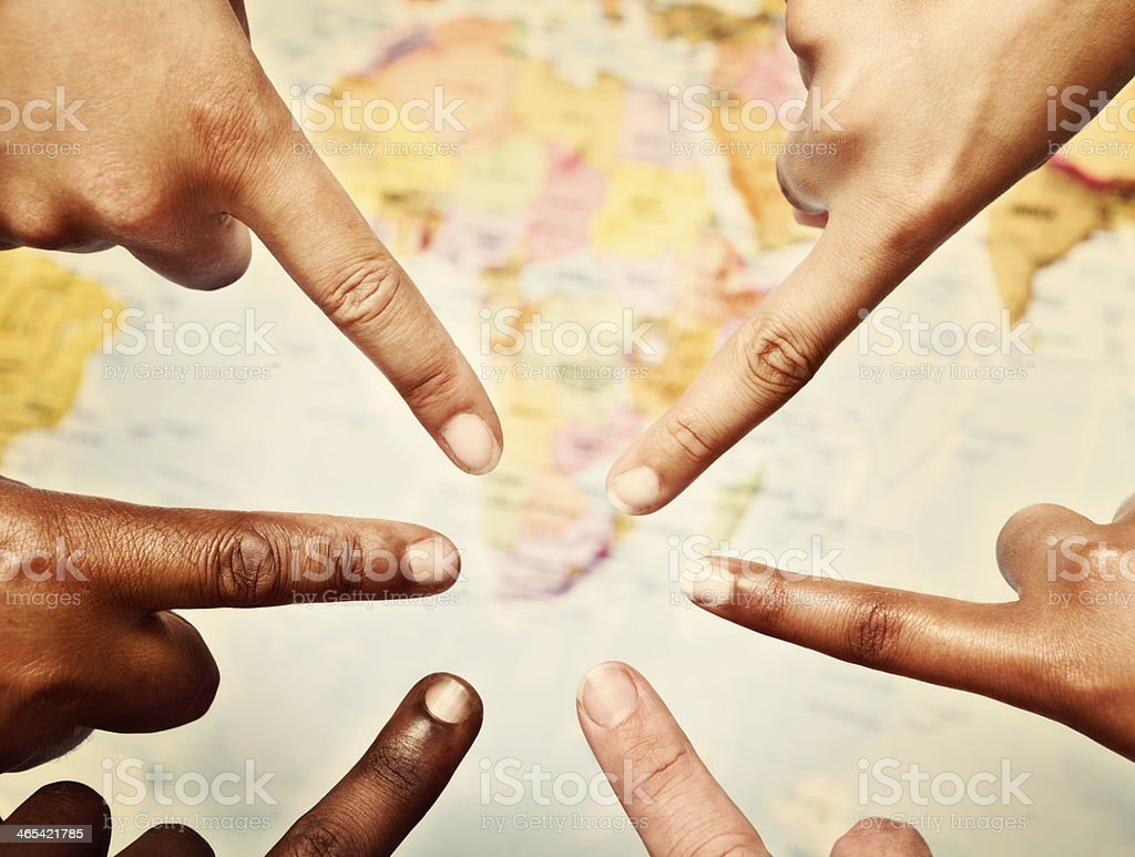 Six hands point out Southern Africa on map stock photo