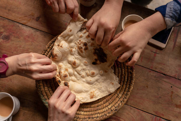 Six hands taking a piece of delicious naan Six hands taking a piece of delicious naan ( Pita bread) on a wooden table naan bread stock pictures, royalty-free photos & images