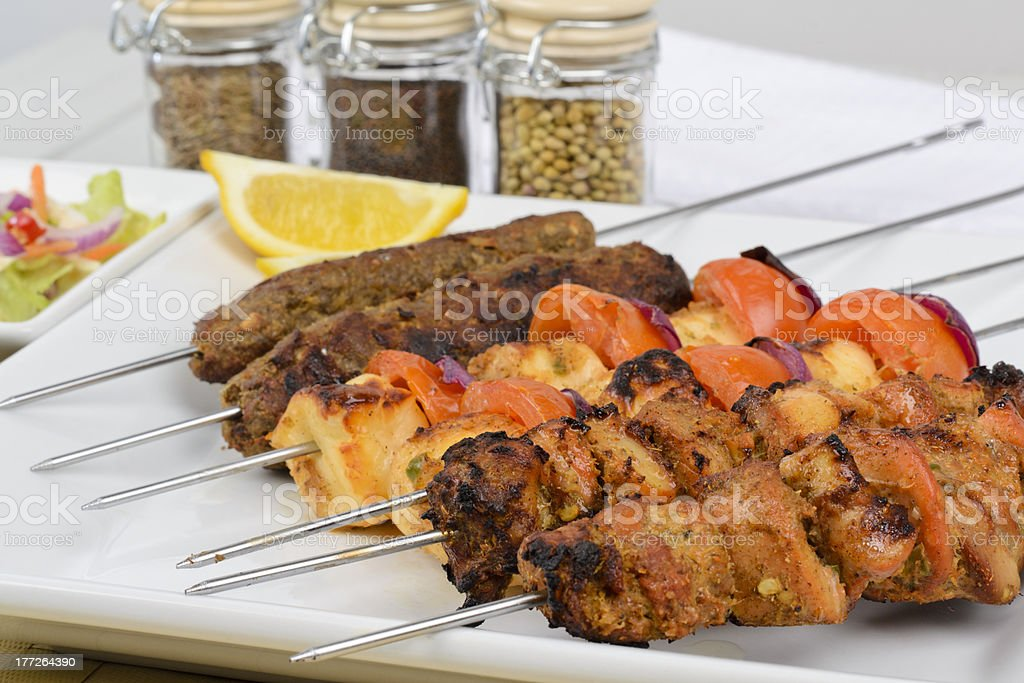 Six kebabs lined up next to spices and a slice of lemon stock photo
