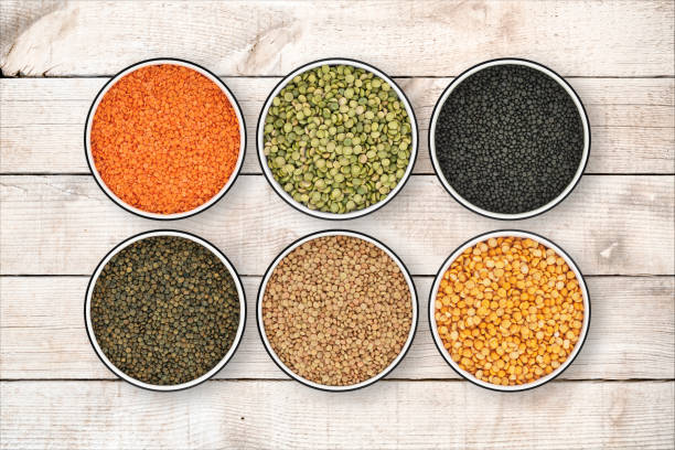 six lentil bowls on wood background from directly above - lenticchie verdi foto e immagini stock