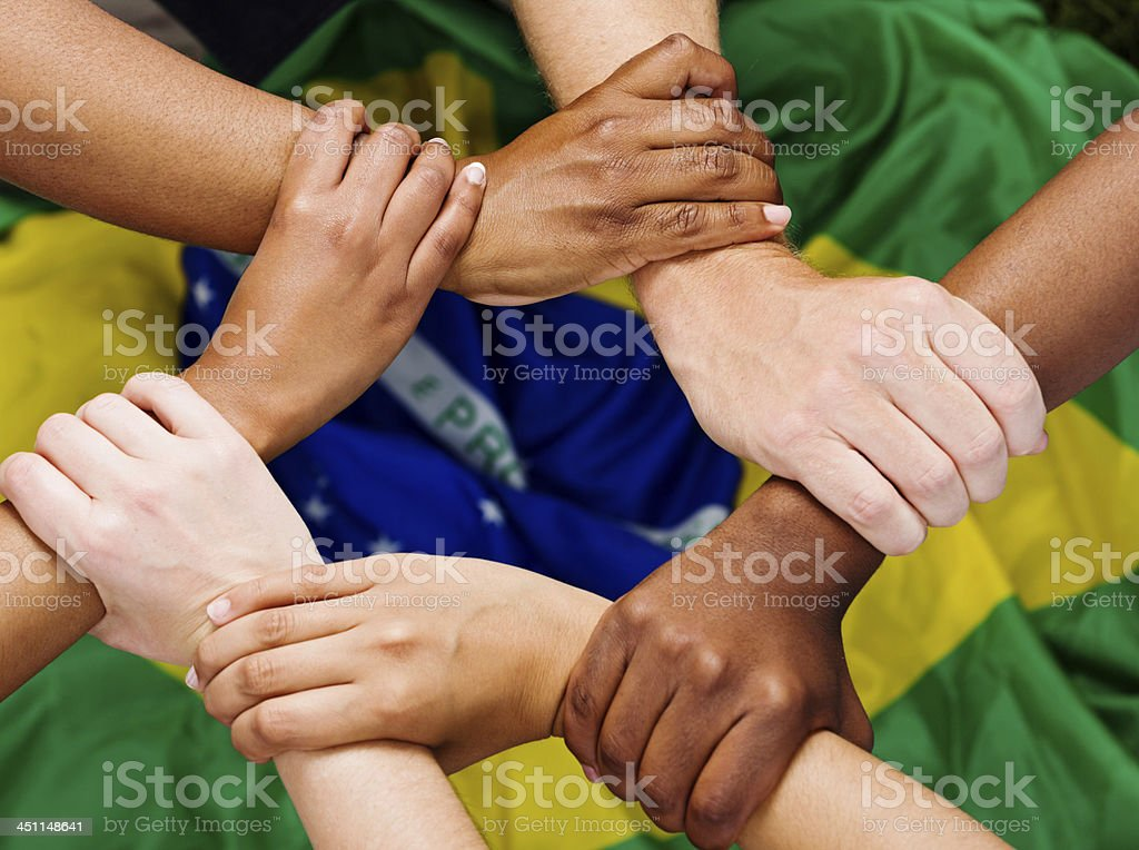Six mixed hands clasped in unity against Brazilian flag royalty-free stock photo