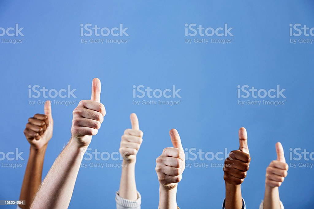 Six mixed hands give thumbs up  of approval and endorsement A group of six male and female hands of many different ethnicities join in giving a hearty thumbs up of approval against a plain blue background, with plenty of copy space.  African Ethnicity Stock Photo