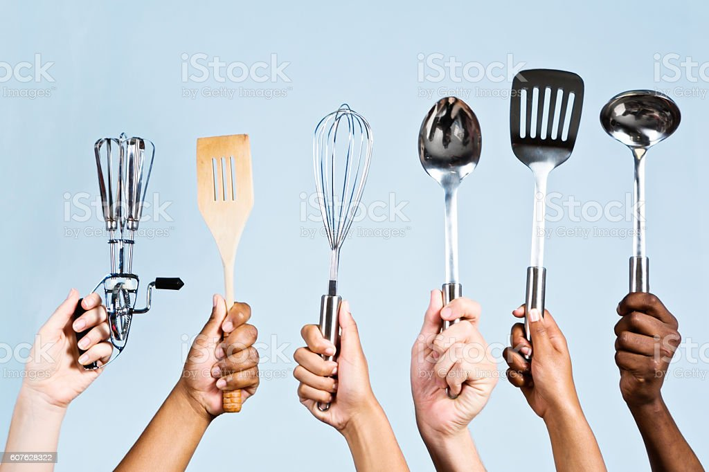 Six mixed hands holding kitchen utensils: master chefs in waiting! stock photo