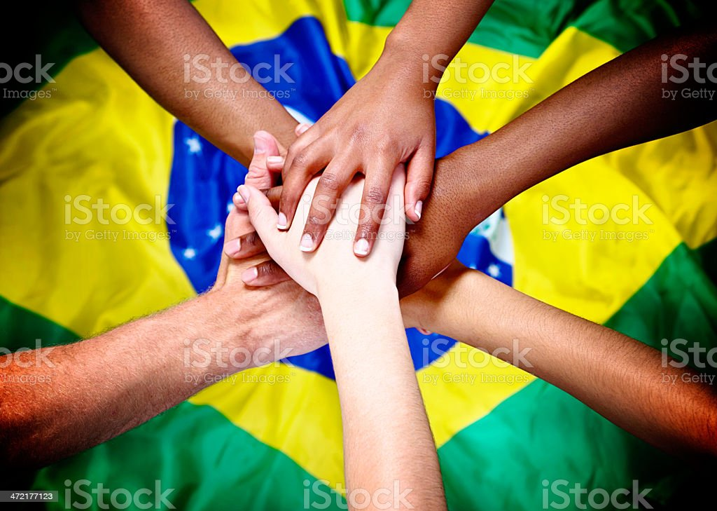 Six mixed hands piled in support over Brazilian national flag stock photo