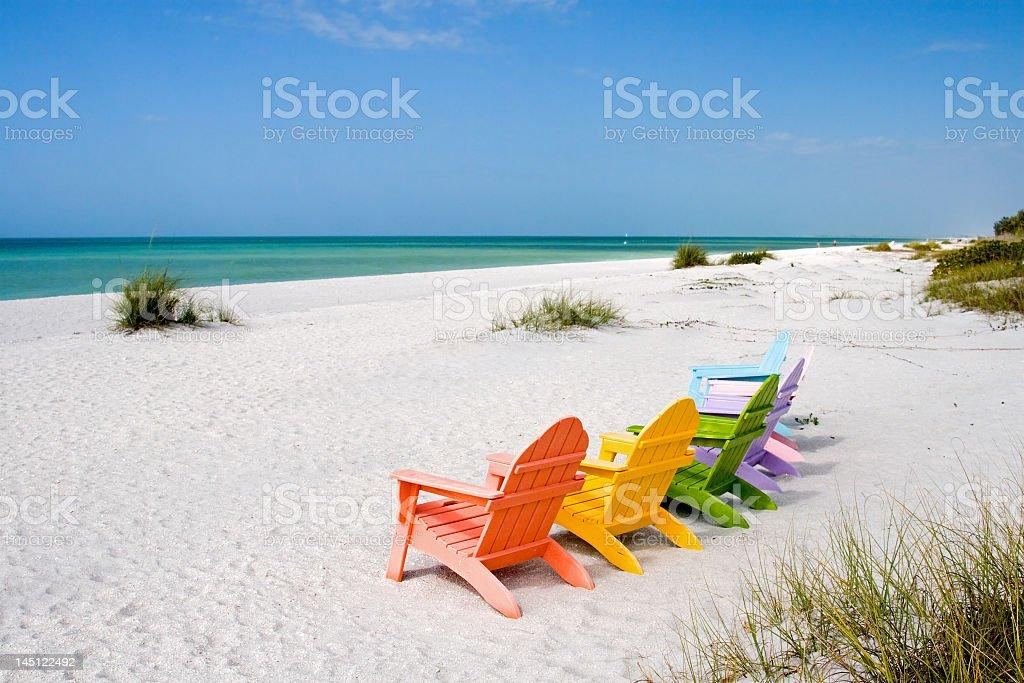 Six multi color chairs set on an empty beach toward the sea  stock photo
