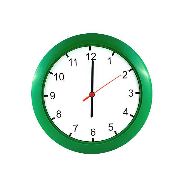 Six o'clock  on green wall clock stock photo