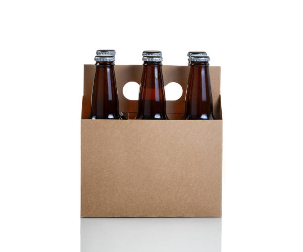 six pack of bottled beer in generic brown cardboard carrier - pack de six photos et images de collection