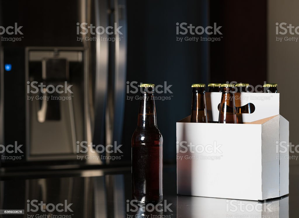 Six pack of brown beer bottles on kitchen counter stock photo