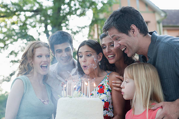 Six people outdoors blowing out candles on a birthday cake stock photo