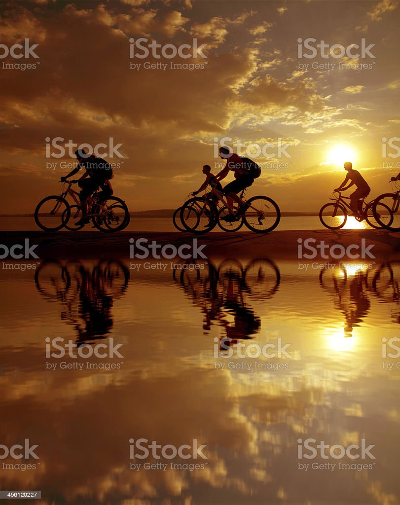 Six people riding bicycles along the shoreline stock photo