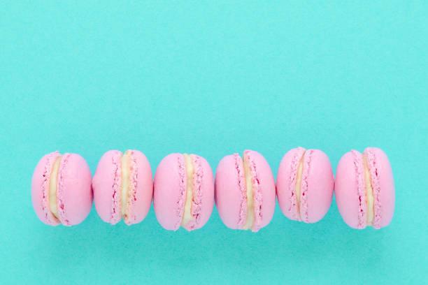 sechs rosa makronen hausgemacht auf türkis hintergrund - lutscher cookies stock-fotos und bilder