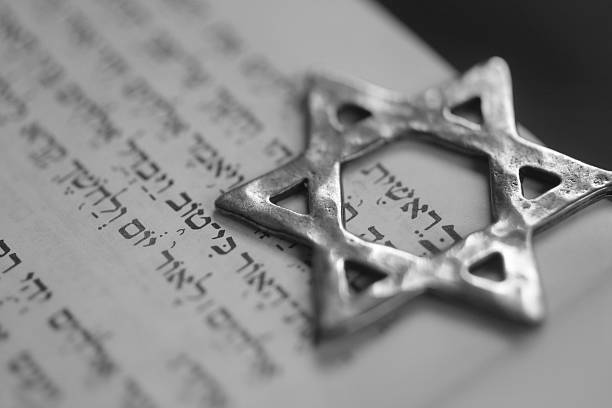 "A six pointed metal star symbol on top of paper ""Ber'eshit"", the first word in the book of Genesis. Macro. judaism stock pictures, royalty-free photos & images"