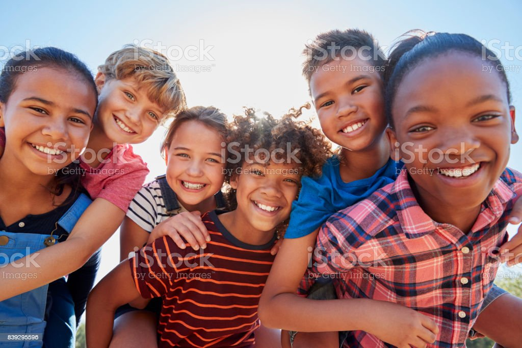 Six pre-teen friends piggybacking in a park, close up portrait stock photo