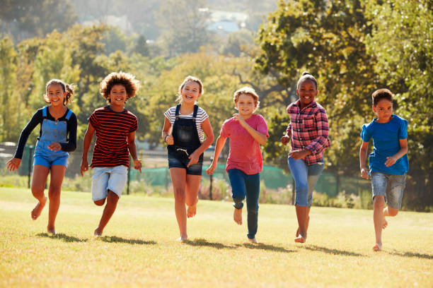 Six pre-teen friends running in a park, front view, close up stock photo