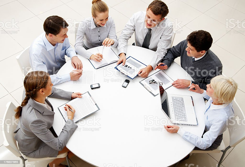 Six professional co-workers sitting around a table working royalty-free stock photo