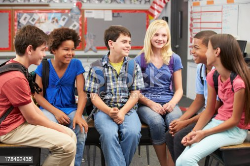 istock Six pupils sitting in a classroom and discussing 178462435