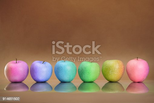 istock Six rainbow colored apples in the row 914651502