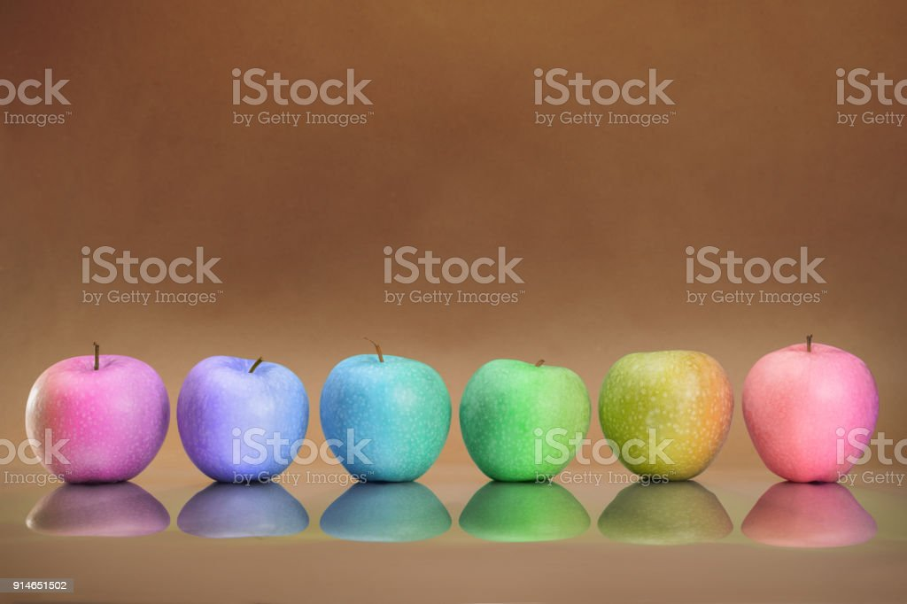 Six rainbow colored apples in the row stock photo