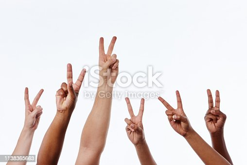 Six mixed hands are raised against white, each making the V-shaped  hand sign for peace or victory.