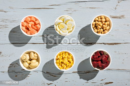 Six ramekins with diced carrot, boiled quail egg, chickpeas, champignon mushrooms, sweet corn and diced beet on a blue rustic wooden table