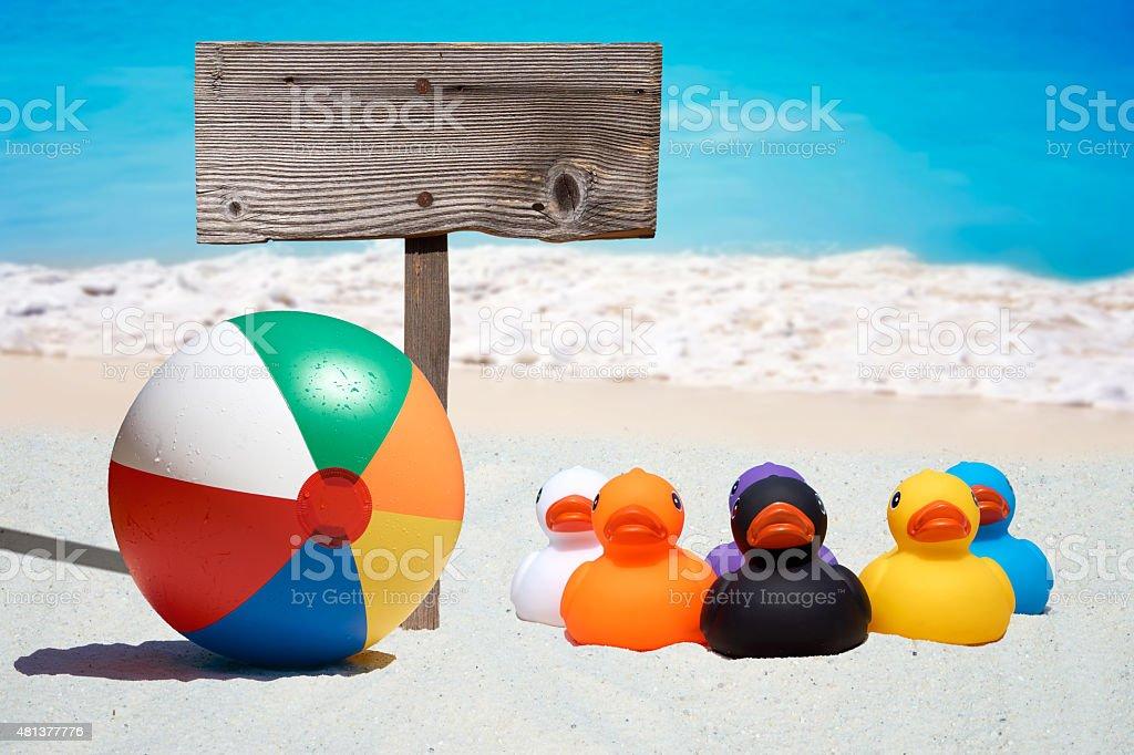 Sei gomma anatre e cartello in legno sulla spiaggia - foto stock