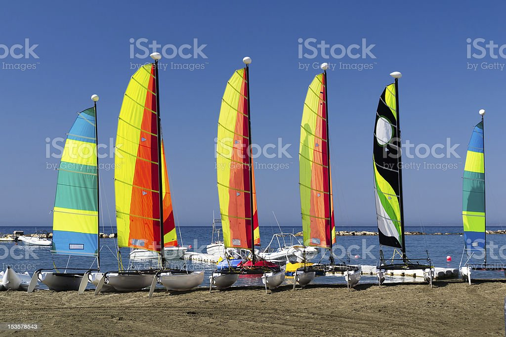 Six sailboats lined up on the shoreline on a clear day royalty-free stock photo