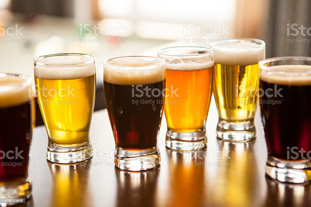 Six sample glasses of beer on a bar stock photo