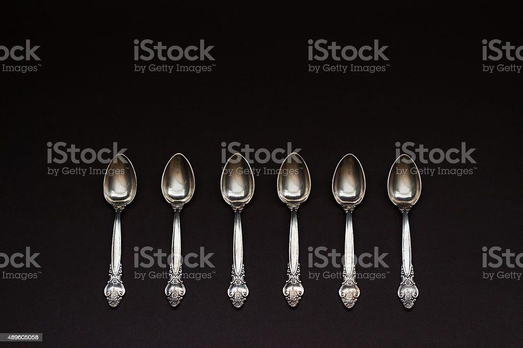 Six silver spoons in a row on black background stock photo