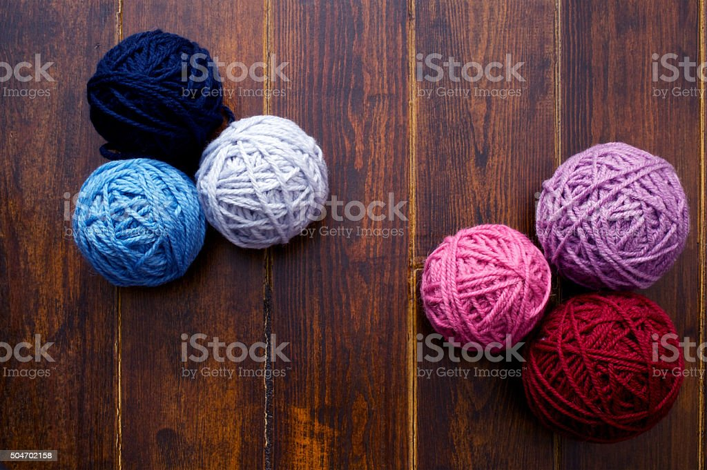 Six skeins in red and blue tones over wooden background stock photo