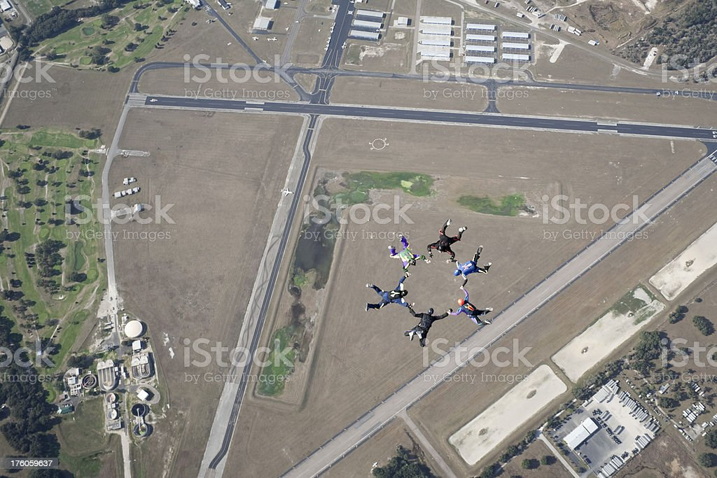 Six skydivers in formation over an airport stock photo