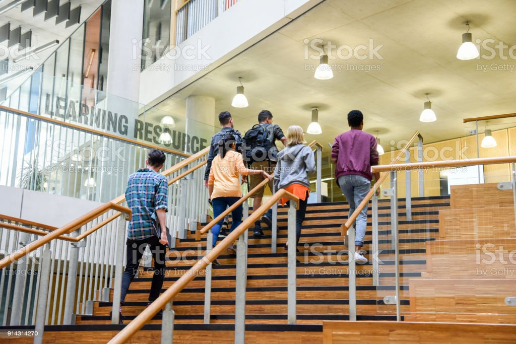 Six students walking up wooden steps in modern college building stock photo
