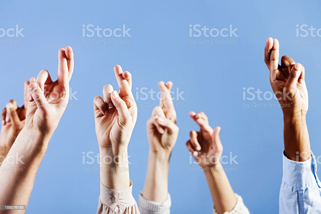 Six superstitious hands, all with fingers crossed, against blue royalty-free stock photo