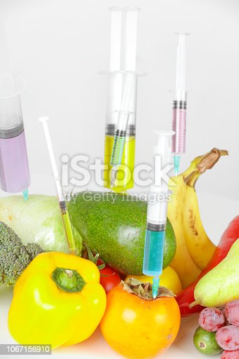 Scientist injecting liquid from syringe into Bananas. Genetically modified organism - apple and laboratory glassware.