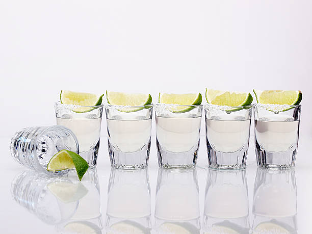 Six tequila shots on a white background Row of Tequila Shot glasses with lime and salt. One down, five to go! tequila shot stock pictures, royalty-free photos & images