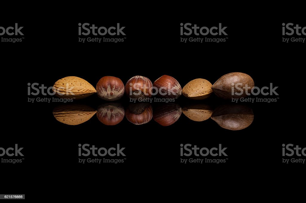 Six unshelled nuts, two almonds, one pecan and three hazelnuts photo libre de droits