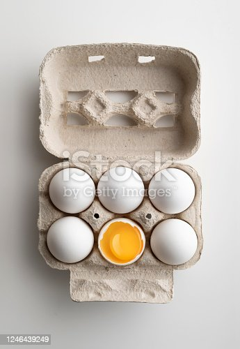 Six white chicken eggs in pater tray with one egg cracked open
