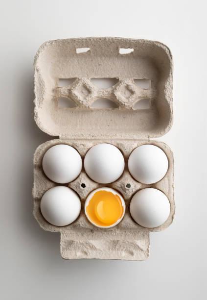Sechs weiße Hühnereier in Pater Tablett mit einem Ei aufgerissen – Foto