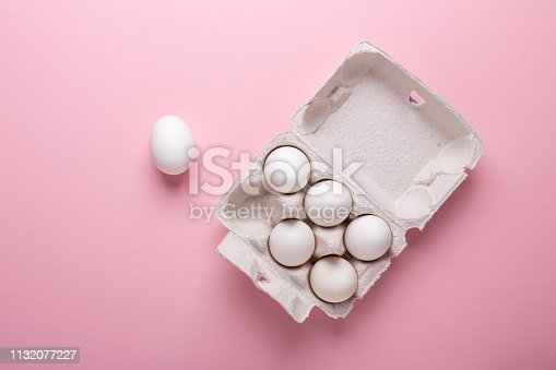istock Six white eggs in carton box on pink paper background Top view Symbol Happy Easter Flat lay 1132077227