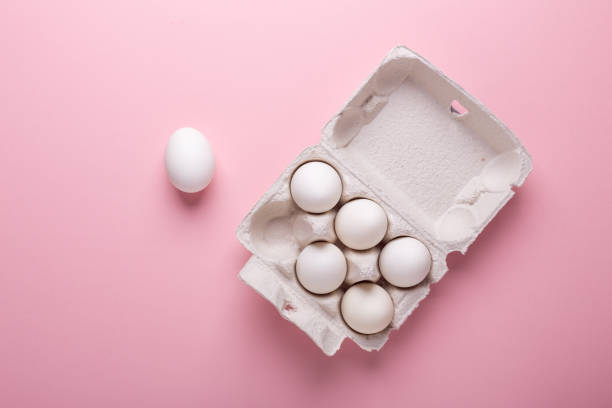 Six white eggs in carton box on pink paper background Top view Symbol Happy Easter Flat lay Six white eggs in carton box on pink paper background Top view Symbol Happy Easter Flat lay Copy space animal egg stock pictures, royalty-free photos & images