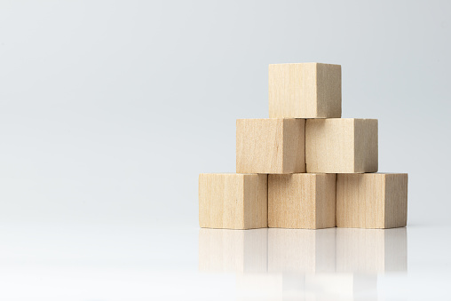 Six wooden blocks arranged in pyramid shape isolated on white background