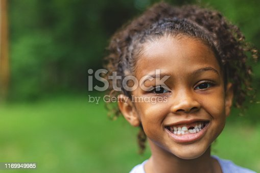Smiling and making faces series 6 year old African American Chinese Ethnicity girl posing for portrait in lush green outdoor back yard setting (Shot with Canon 5DS 50.6mp photos professionally retouched - Lightroom / Photoshop - original size 5792 x 8688 downsampled as needed for clarity and select focus used for dramatic effect)